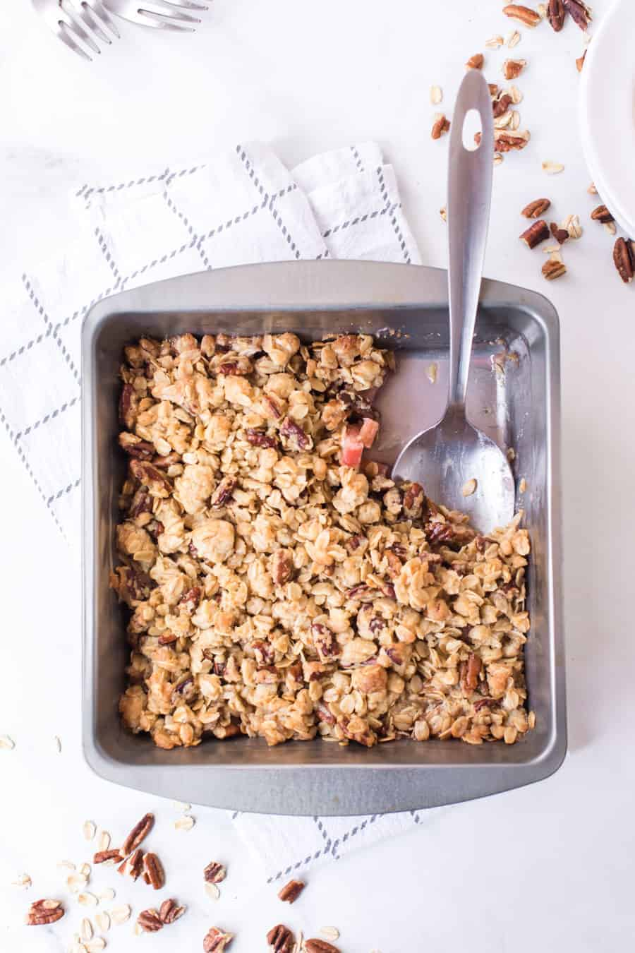 rhubarb crisp in baking pan with serving spoon on white towel and white countertop with pecans