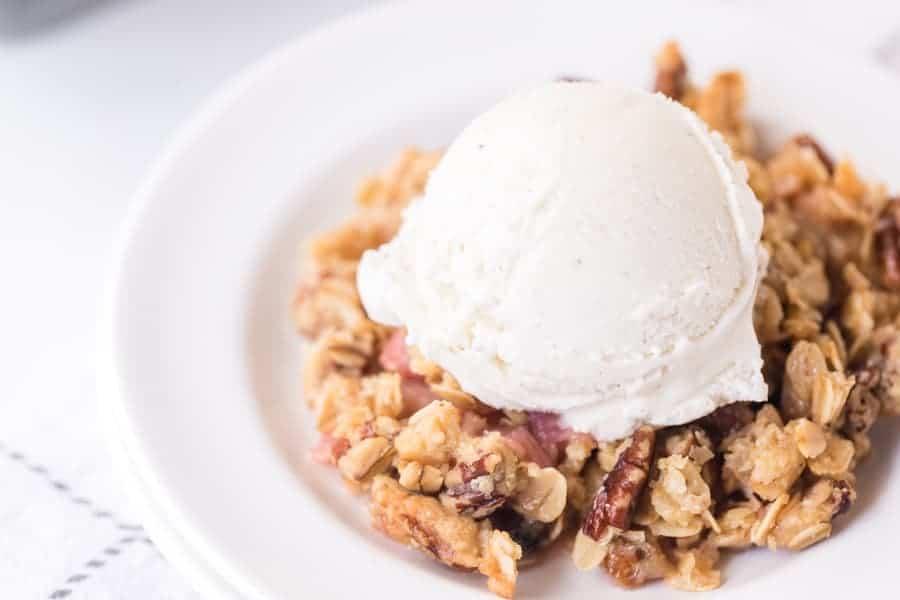 closeup shot of rhubarb crisp on round white plate with scoop of vanilla ice cream
