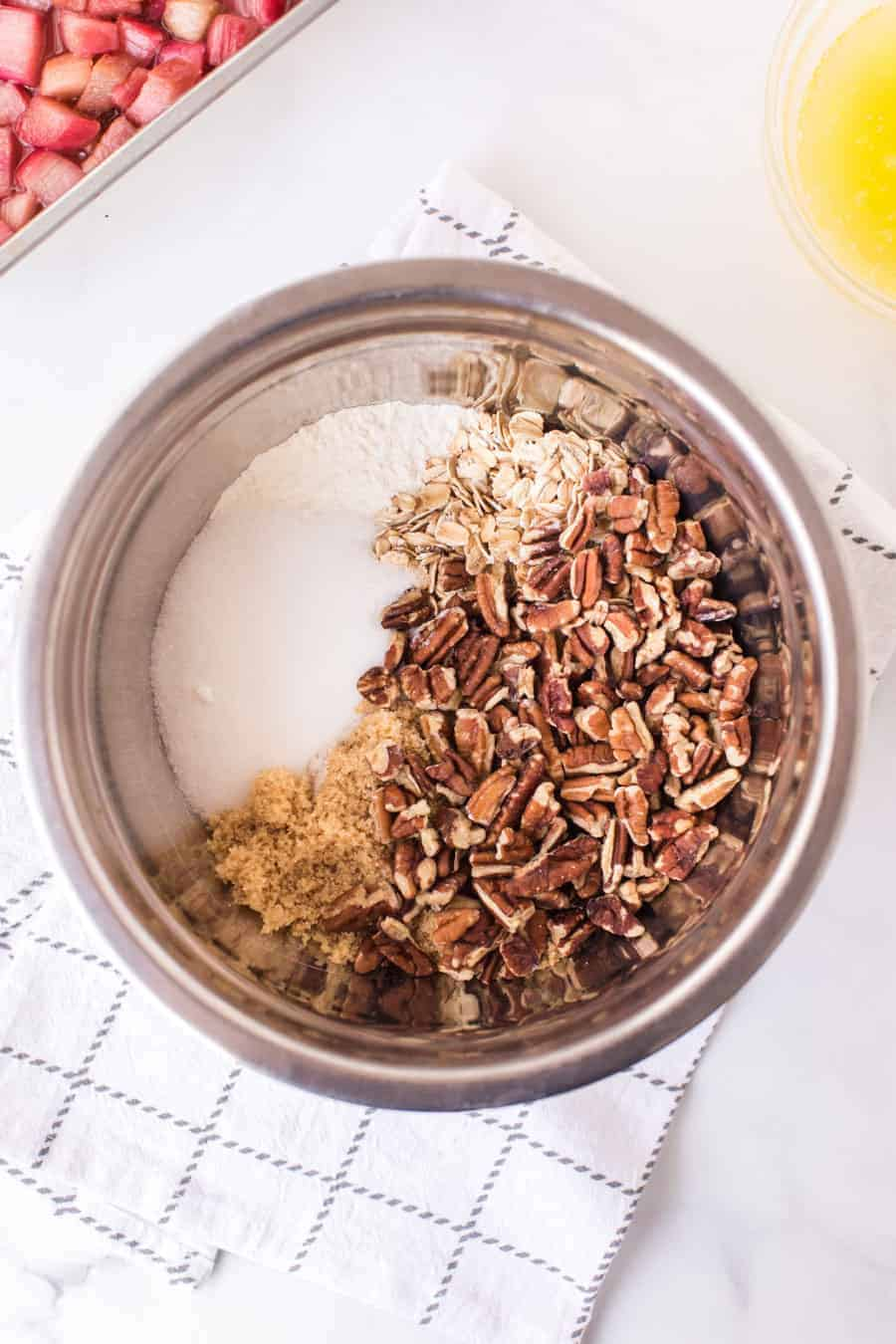 mixing bowl with chopped pecans brown sugar and oats