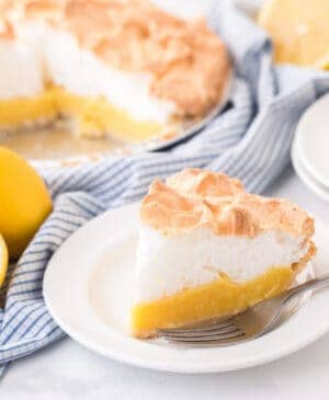 closeup of lemon meringue pie on white plate with fork next to lemons and pie