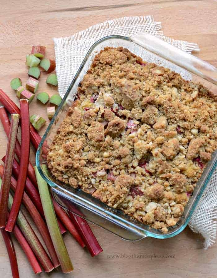 Rhubarb Crumb Bars in a glass pan with chopped rhubarb to the side