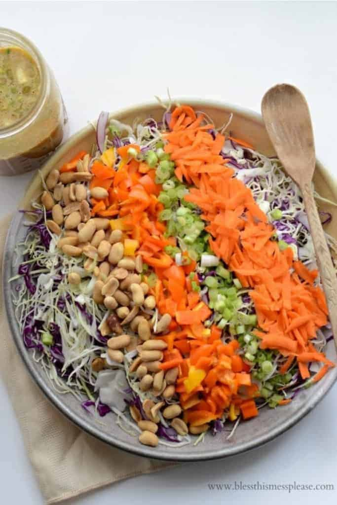 A serving bowl of chopped Asian peanut salad with rows of shredded cabbage, peanuts, chopped bell peppers, scallions, and shredded carrots