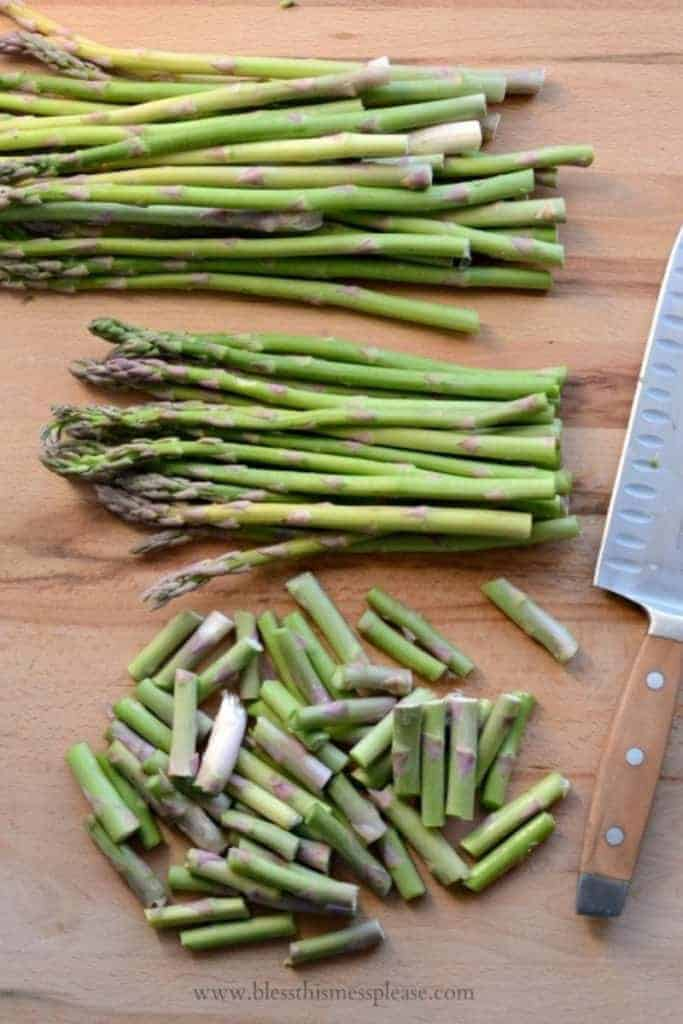 Fresh asparagus on a cutting board with ends trimmed off