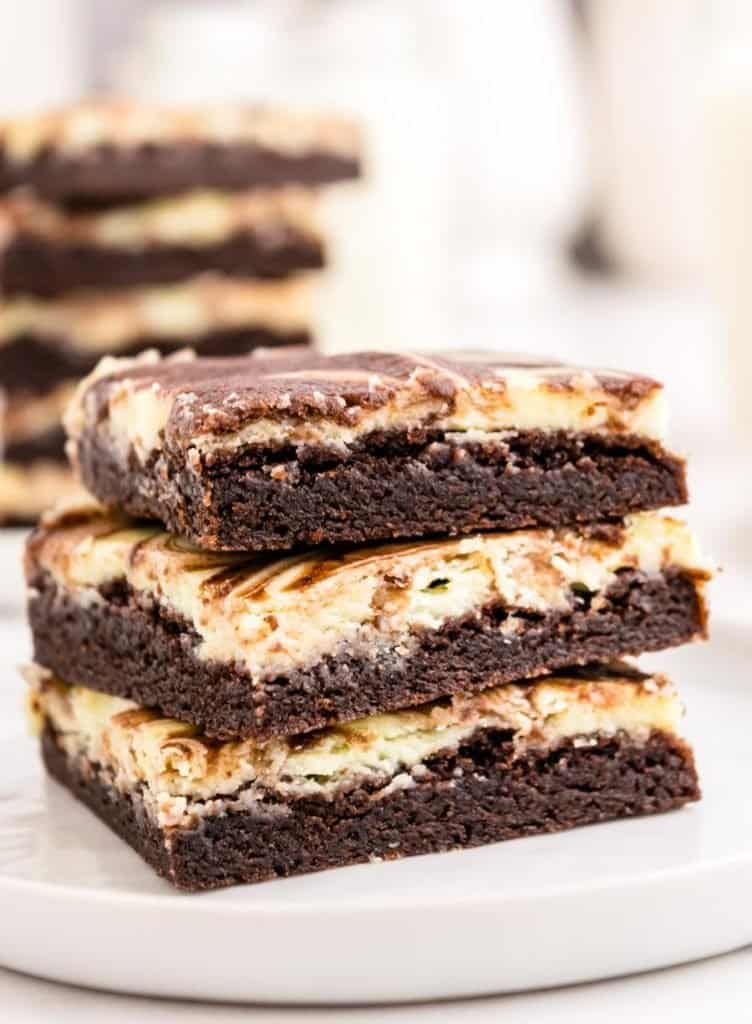 cheesecake brownies stacked on a plate