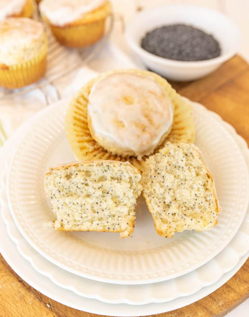 picture of a lemon poppy seed muffin cut in half and another lemon poppy seed muffin on a plate