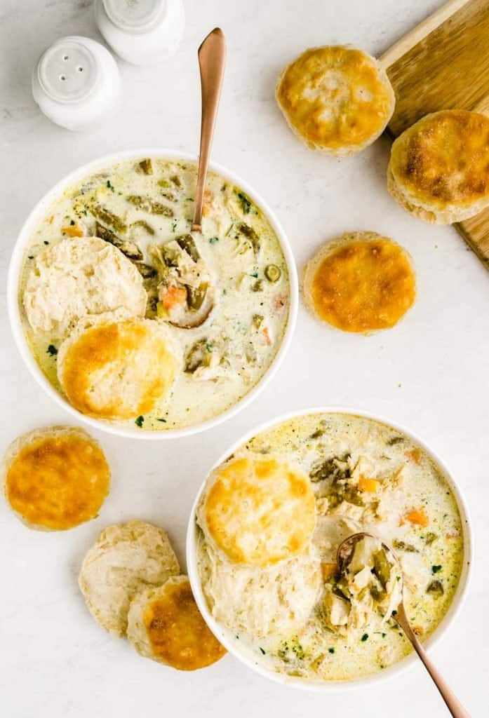 top view of two bowls of slow cooker chicken pot pie with biscuits around the bowls