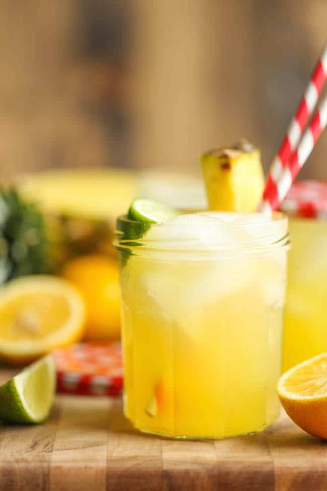 A glass of pineapple lemonade with two straws, fresh pineapple and a lime wedge