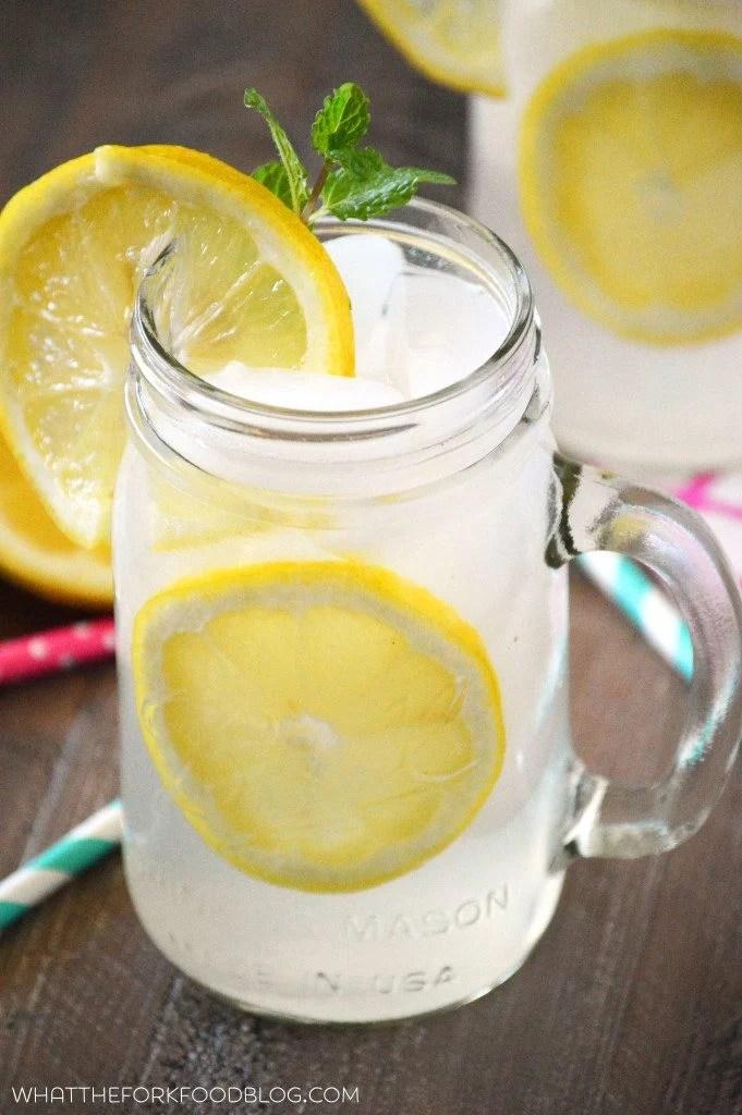 A mason jar of homemade lemonade with a lemon slice and sprig of fresh mint