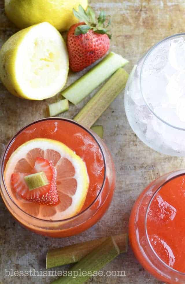 Two glasses of strawberry rhubarb lemonade surrounded by pieces of rhubarb, lemon halves and a whole strawberry