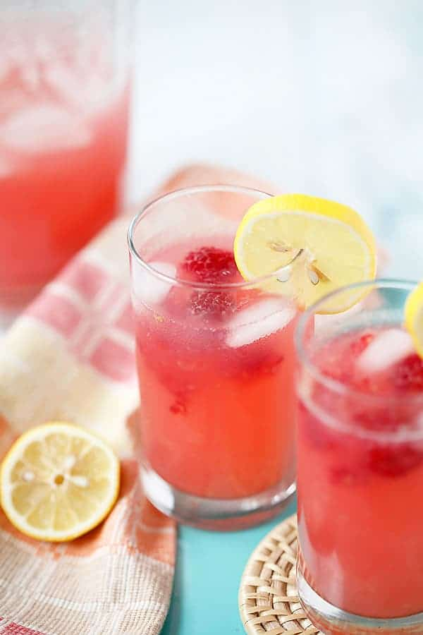 Two glasses of raspberry lemonade with fresh raspberries and a lemon slice