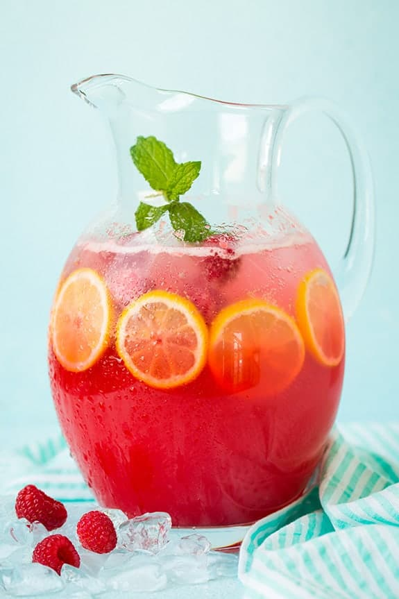 A pitcher of sparkling raspberry lemonade with lemon slices, fresh raspberries and a mint leaves