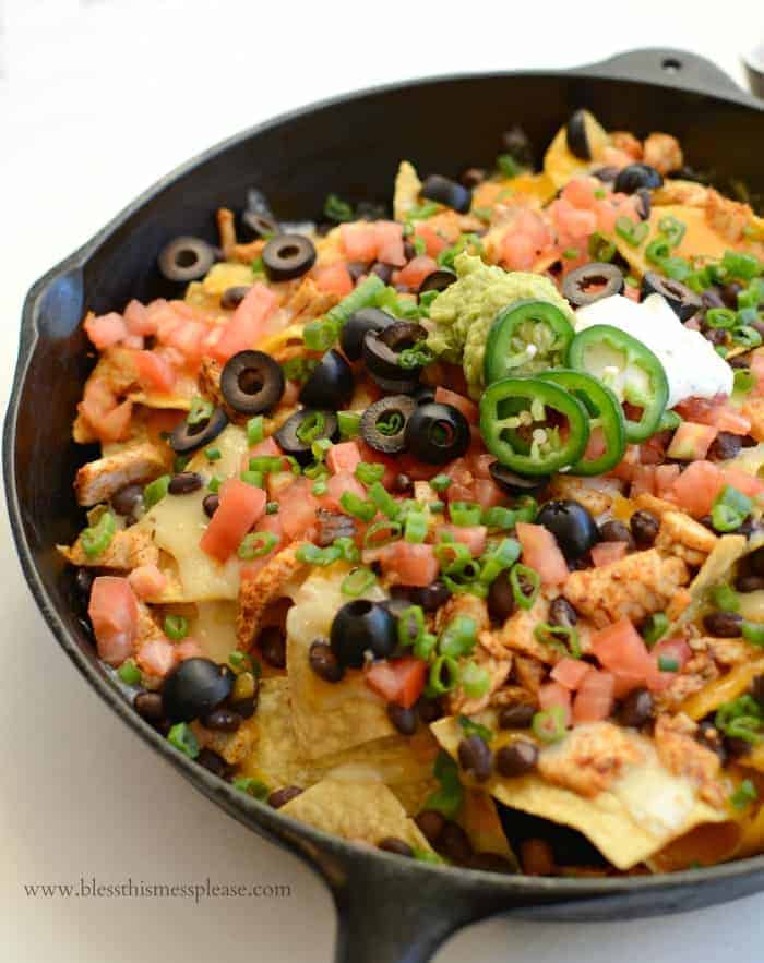 Skillet of chicken nachos with peppers, tomatoes, olives, and more