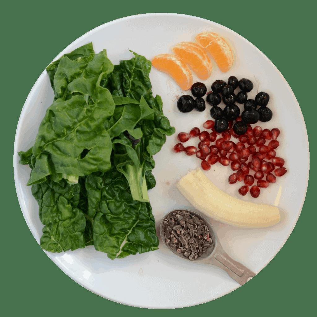 banana, orange, blueberries, pomegranate, cocoa nibs, and greens