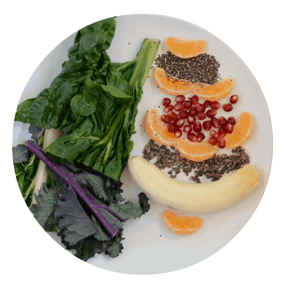 banana, oranges,pomegranate, chia seeds, and greens on a plate