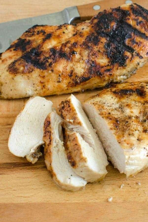 Grilled seasoned whole chicken breast on a cutting board with a few sliced pieces