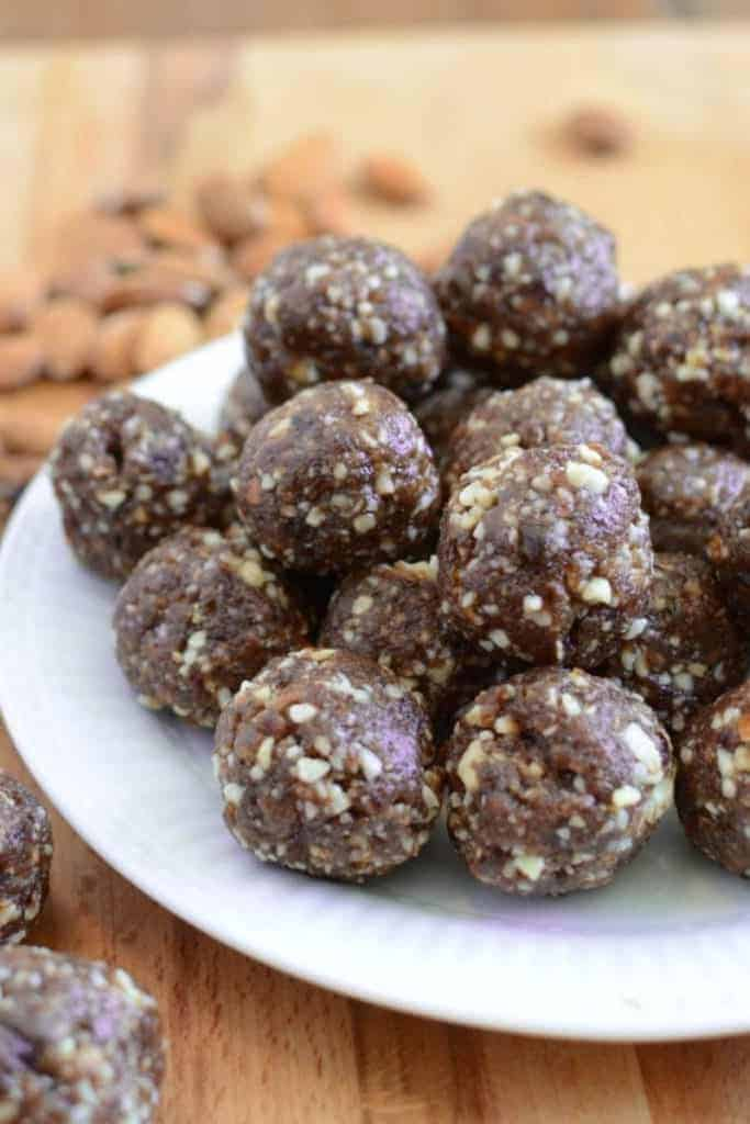 A plate of cherry energy balls with chopped nuts