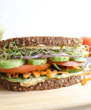 The Ultimate Hummus and Veggie Sandwich piled high with veggies and sprout, loaded with creamy hummus, and held together with sturdy whole grain bread. Meatless sandwiches never looked so good!