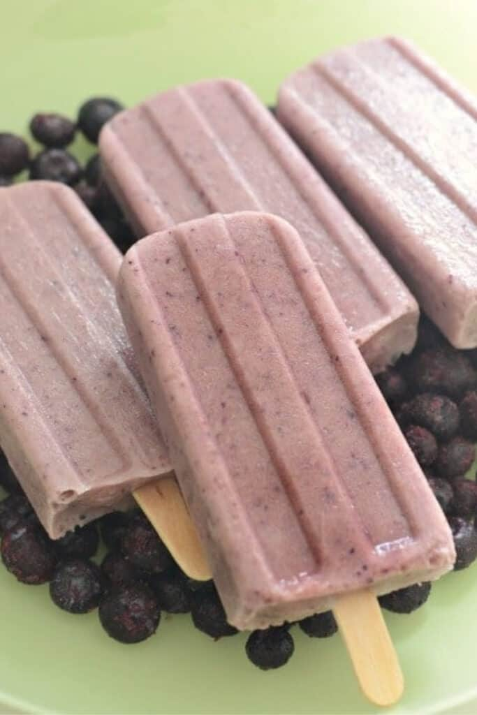 Four homemade blueberry popsicles on a green plate with whole blueberries