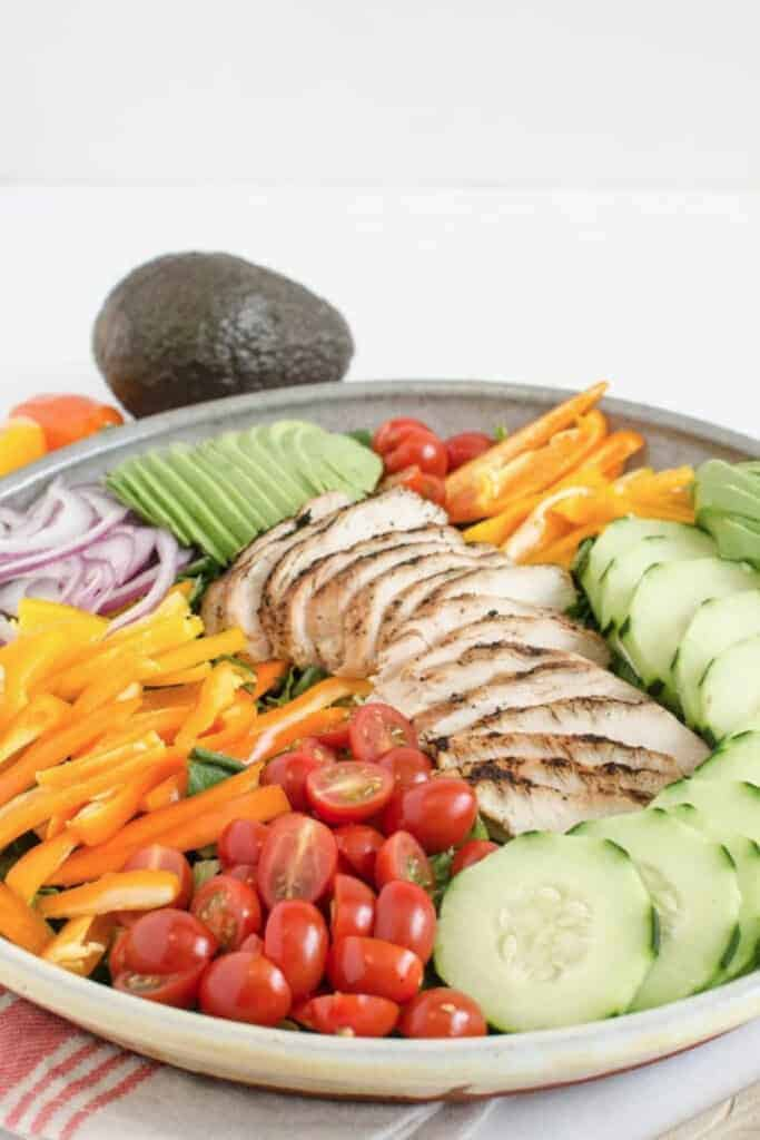 A large serving bowl of salad topped with a variety of colorful vegetables and sliced grilled chicken