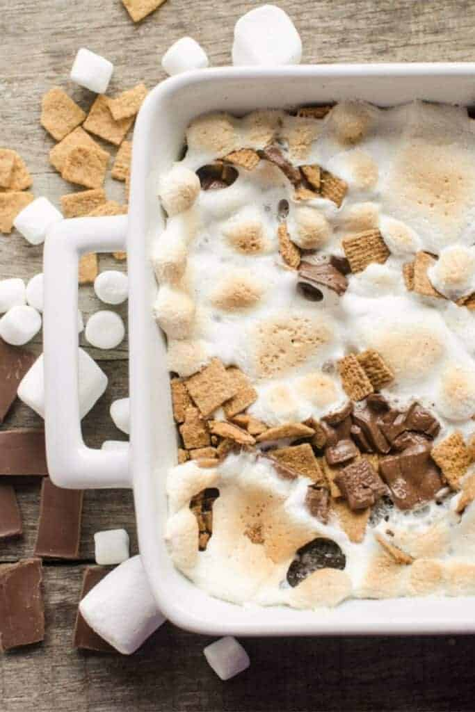 A baking pan of smores brownies with golden melted marshmallows, chocolate pieces, and graham cereal squares