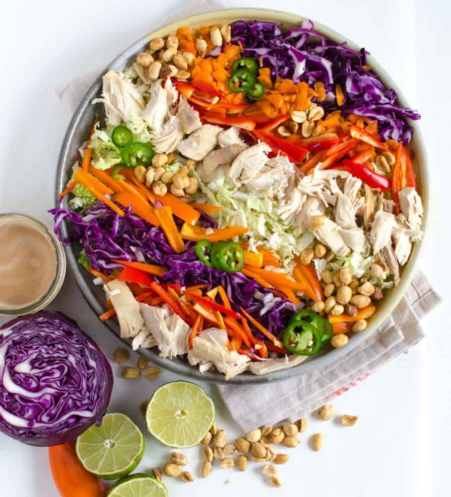 A bowl of colorful Asian Chicken Salad and a bowl of Peanut Lime Dressing
