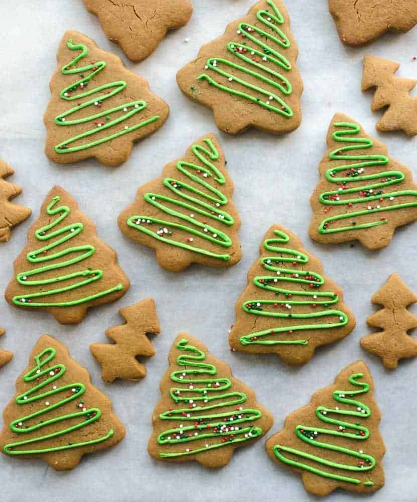 gingerbread cookies cut out like trees and decorated with green icing and sprinkles on white paper