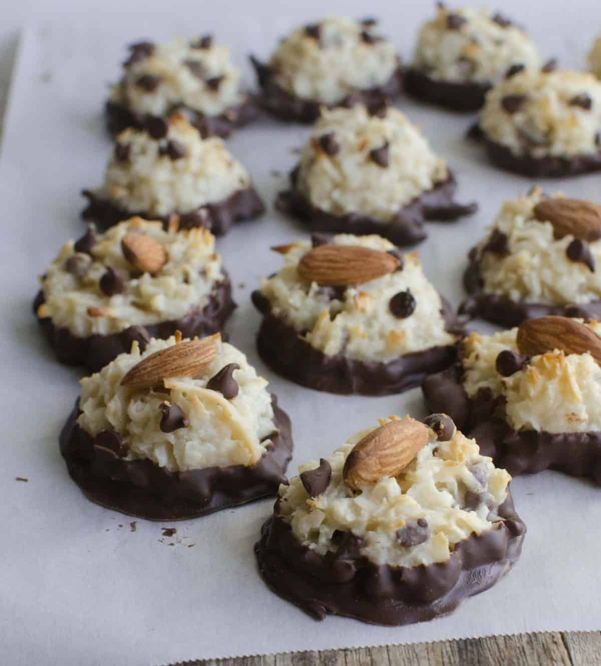 chocolate dipped macaroons topped with mini chocolate chips and an almond