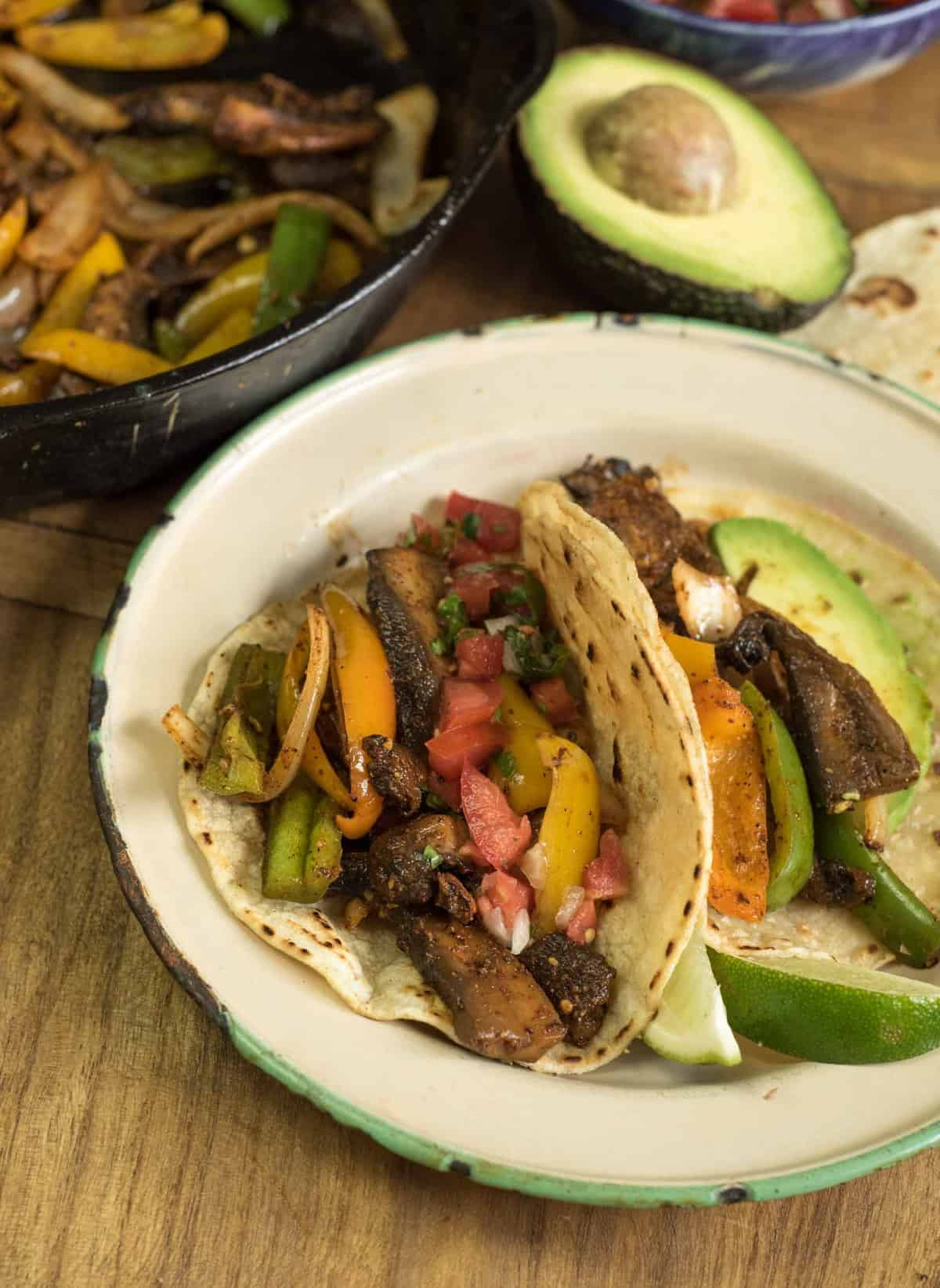tacos on a plate with an avocado to the side