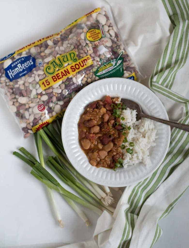 beans and rice in a white bowl with a bags of hurst's cajun 15 bean soup bean mix and green onions on the side
