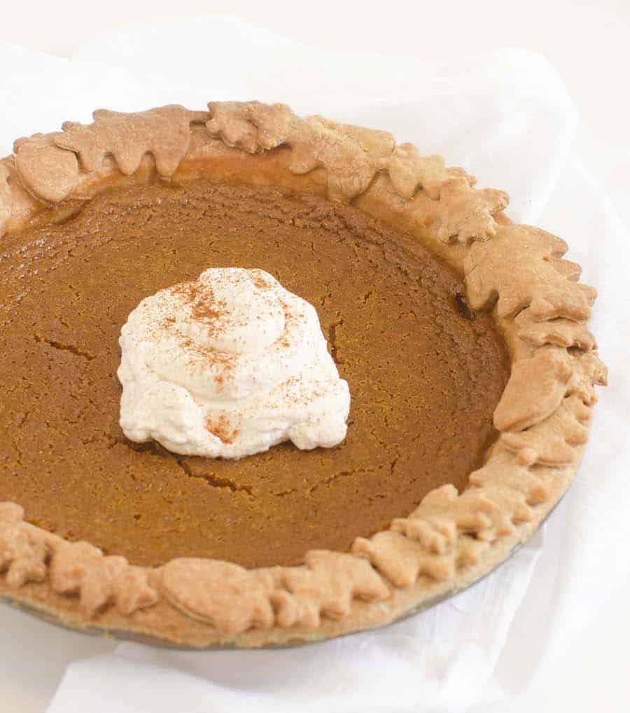 pumpkin pie in a glass pie pan on a bright white towel