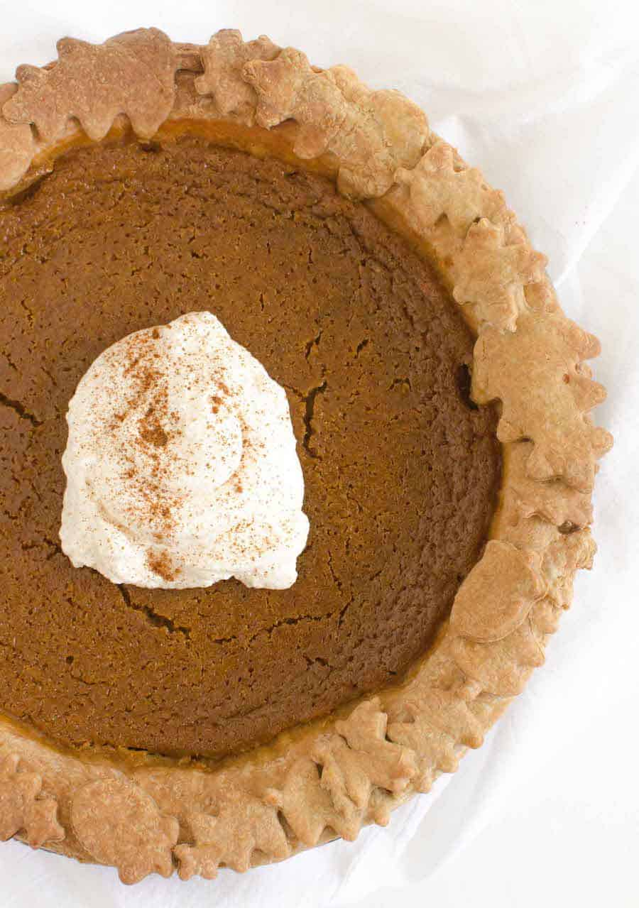 pumpkin pie with a dollop of whipped cream and cinnamon sprinkled on top