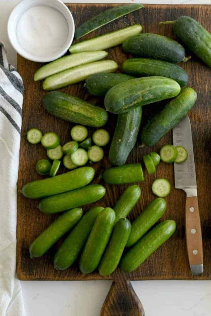 A wooden cutting board with whole mini cucumbers, sliced mini cucumbers, and spears of mini cucumbers with a knife and a small bowl of salt