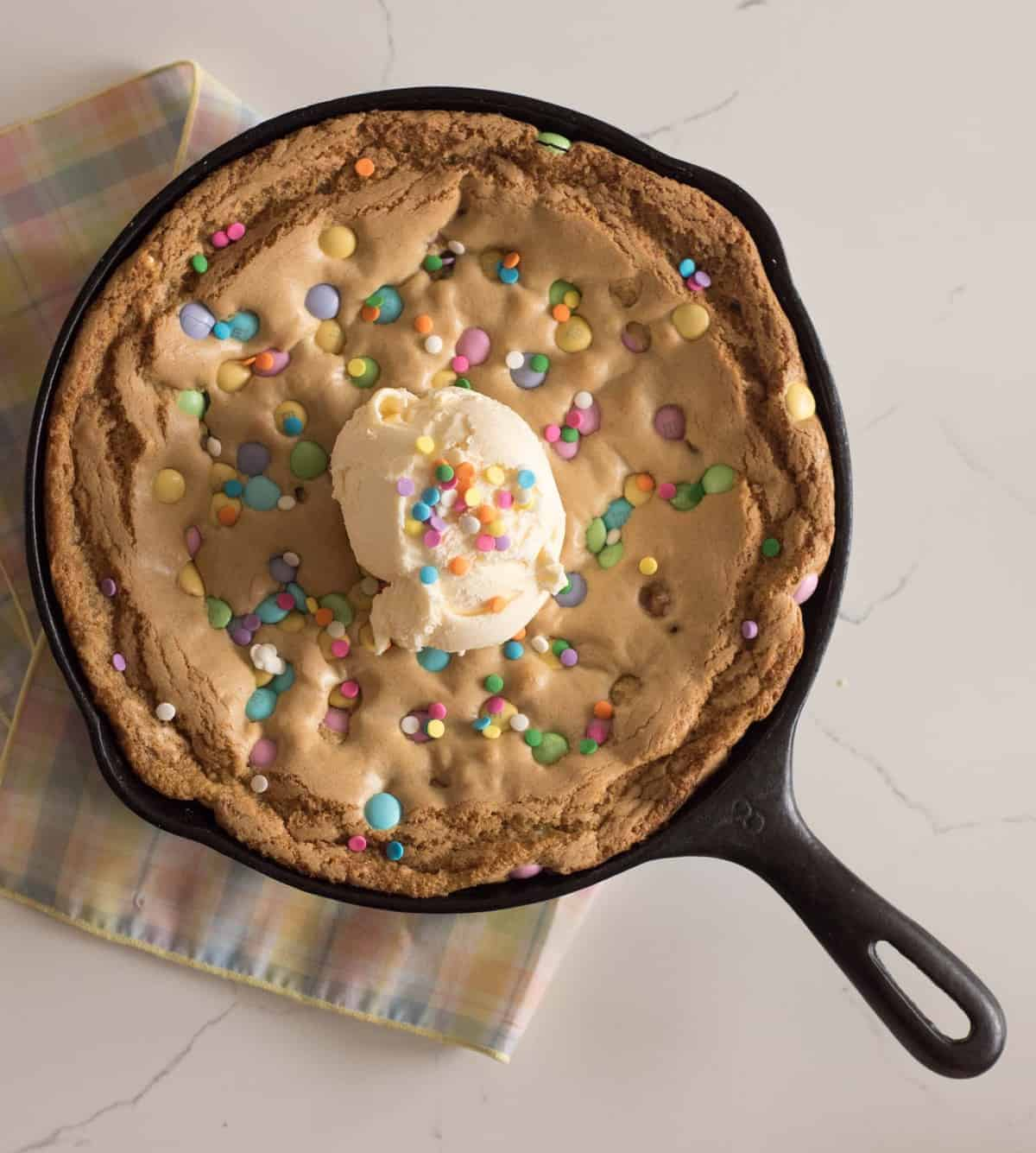 Easy skillet cookie recipe that is baked in a cast iron skillet topped with ice cream and sprinkles.