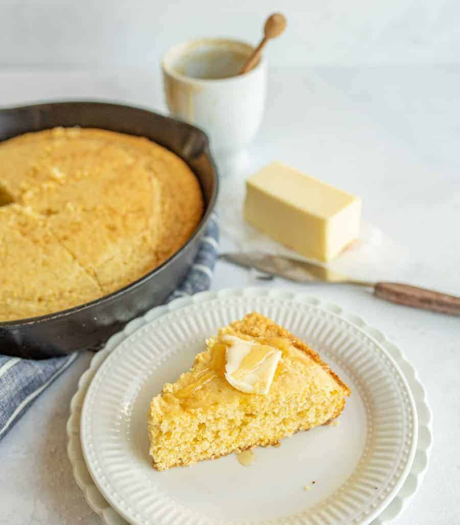 slice of cornbread on plate with honey and butter on top