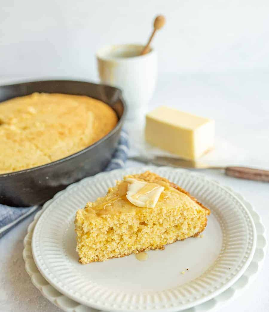 slice of cornbread with butter and honey on top with pan of cornbread behind it