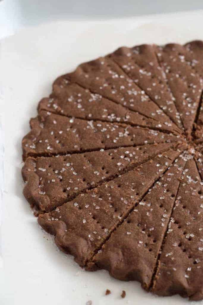 A round wheel of chocolate shortbread cookies with coarse sugar cut into wedges
