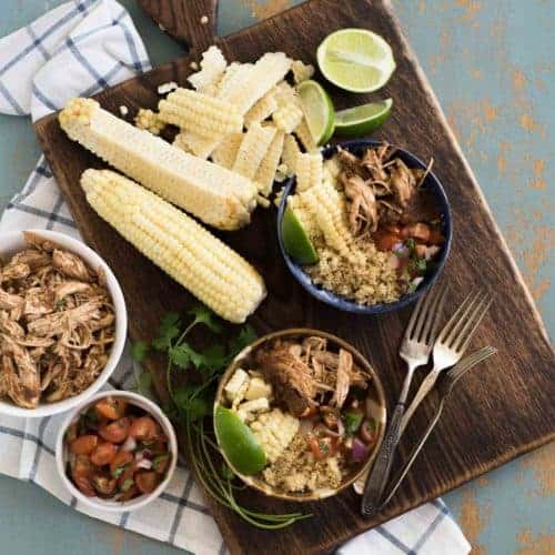 A wooden board with two chipotle chicken burrito bowls with corn on the cob, lime wedges, cilantro, a bowl of shredded chicken, and a bowl of grape tomatoes