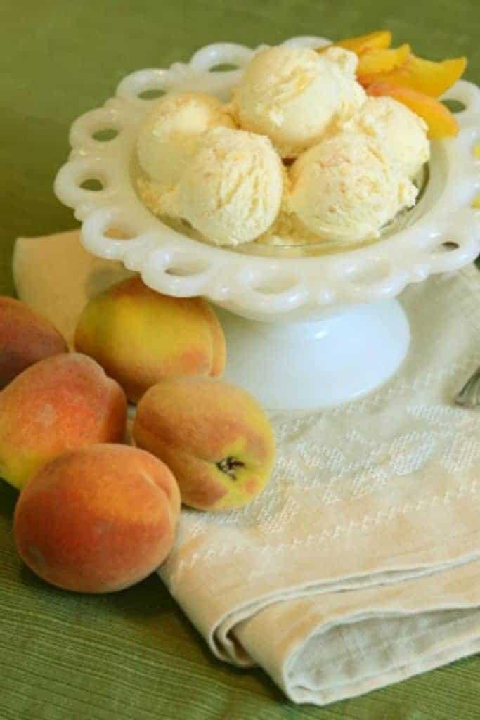 A few scoops of fresh peach ice cream with fresh peach slices in a decorative white dish