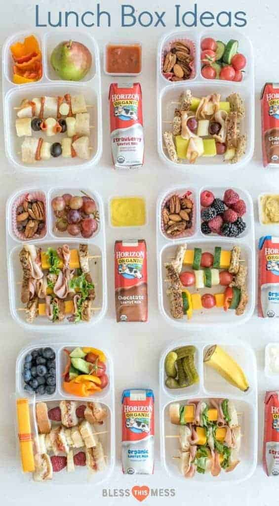 Six divided lunch containers with a variety of sandwiches on a stick, assorted vegetables and fruits and Horizon Organic Milk boxes