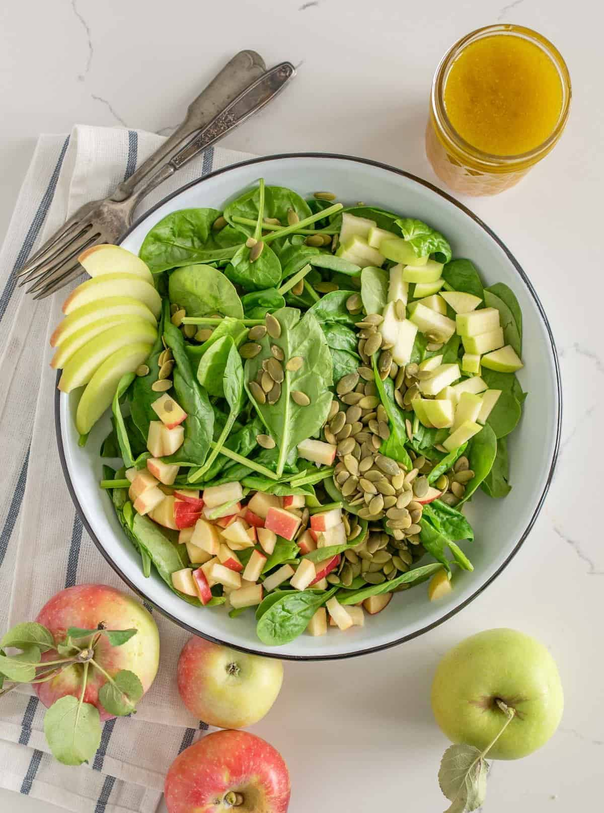 Bowl of spinach salad with apples and apple vinaigrette