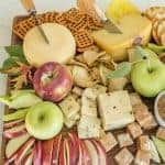 Platter with cheese, apple slices, crackers, and caramel dip