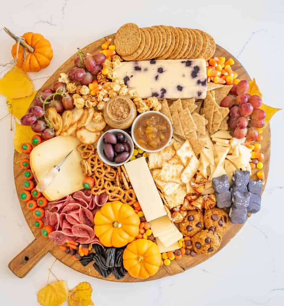 Top view of a round Halloween Cheese Board with crackers, pretzels, cheeses, meats, fall-colored candies, mini gourds