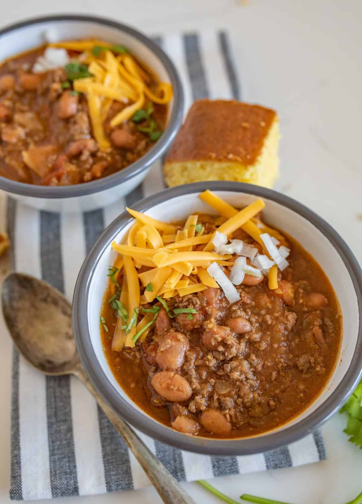 Two bowls of slow cooker chili with cornbread
