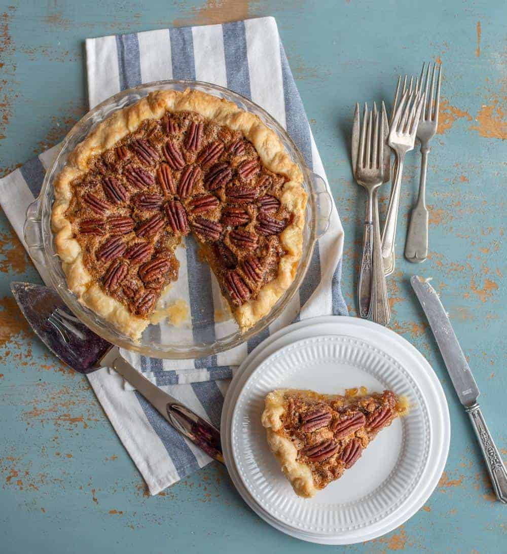 An overhead shot of a pecan pie in a clear dish on top of a folded blue and white striped dish towel. On the lower left hand side of the pie is a silver pie cutter. To the right of the pie are varying sizes of silver forks. Under the forks is a slice of the pecan pie that is on a fancy white plate. Under that plate are varying sizes of plain white dishes. On the right side of the slice of pie is a silver butter knife. These are all resting on a turquoise painted table that has wood showing through in spots.