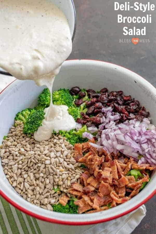 Title Image for Deli Style Broccoli Salad and a serving bowl with separate broccoli salad ingredients, including broccoli, bacon, diced red onion, dried cranberries, sunflower seeds and a creamy dressing