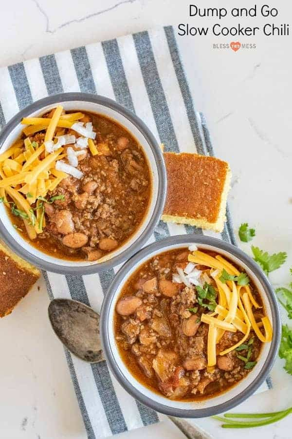 Title Image for Dump and Go Slow Cooker Chili and two bowls of chili topped with shredded cheese, diced onion and cilantro