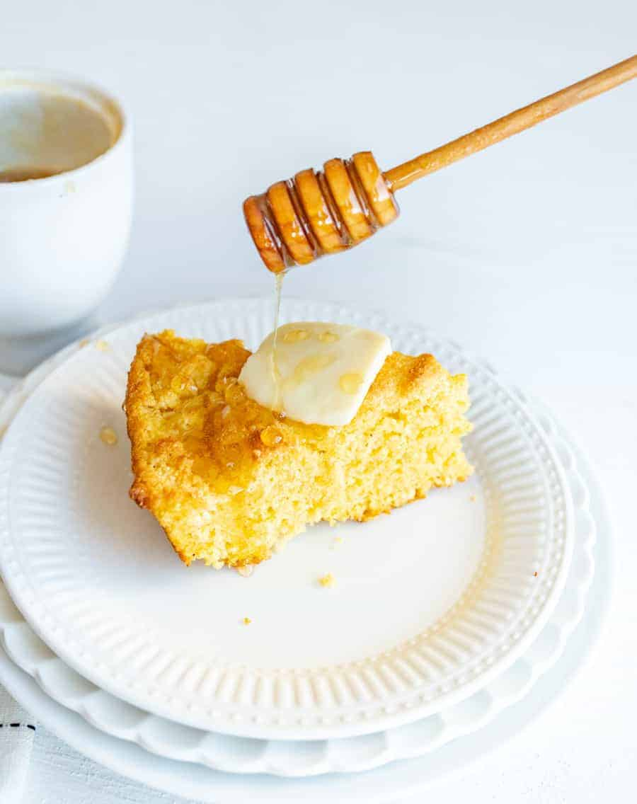 Skillet Cornbread with butter and honey drizzle on round white plate