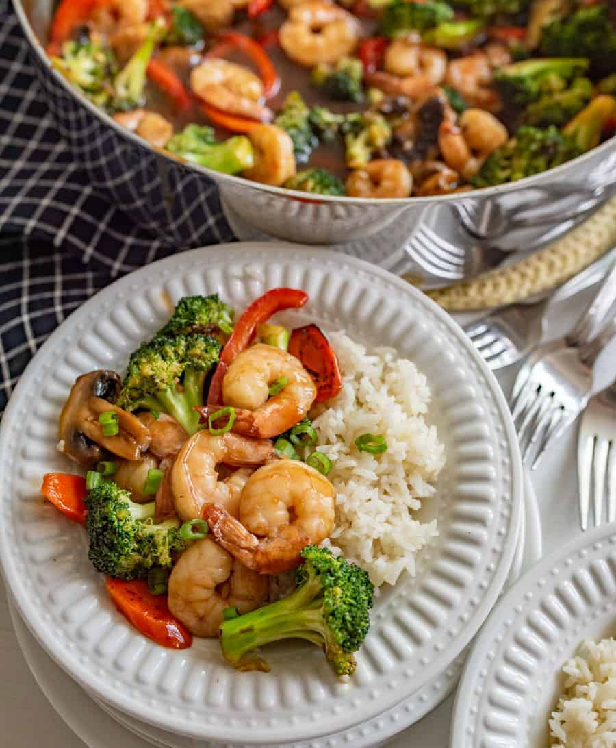 shrimp and veggies with white rice on white plate next to pot of shrimp and vegetables and forks