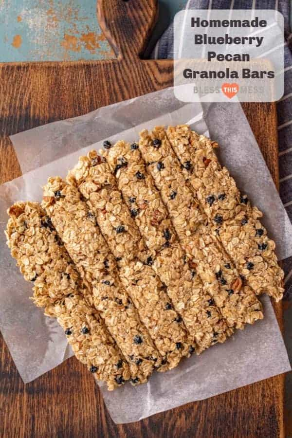 Title Image for Homemade Blueberry Pecan Granola Bars and a square of cut blueberry pecan granola bars on a wooden cutting board with wax paper