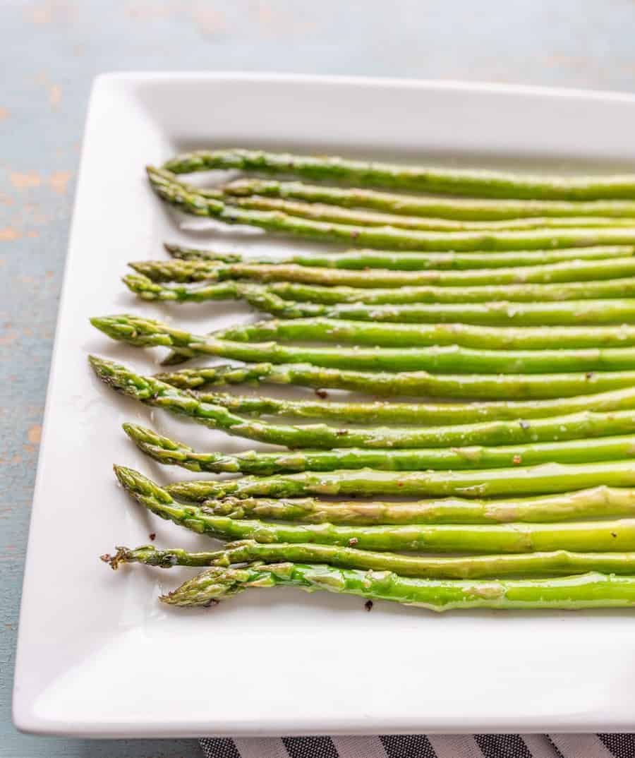 Bright green crisp cooked asparagus on a white plate shining with a bit of cooking oil and sprinkled with salt and pepper.